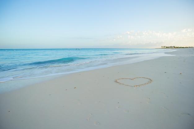 Сердце окрашены в белый песок на тропическом пляже Premium Фотографии