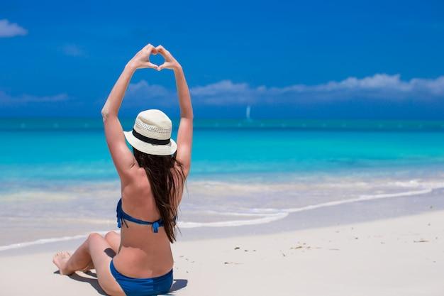 Красивая молодая женщина, делая сердце с руками на пляже Premium Фотографии