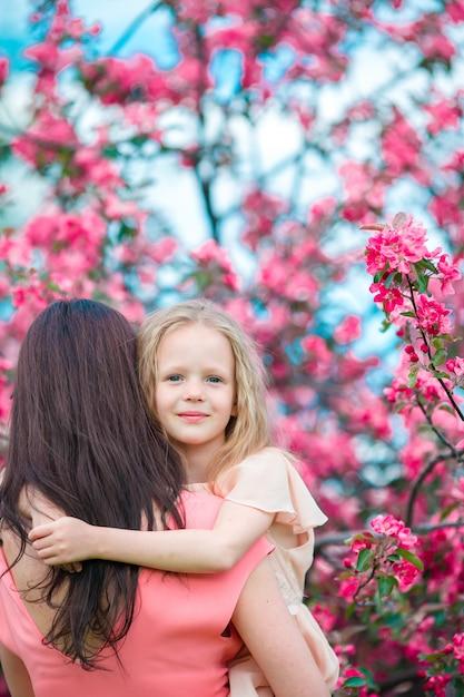 春の日に咲く桜の庭で若い母親とかわいい女の子 Premium写真