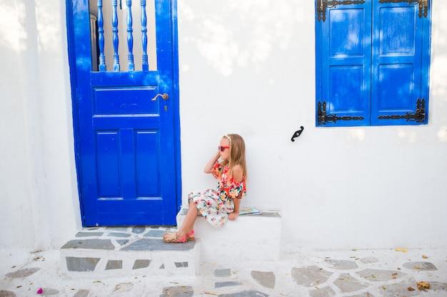 Маленькая девочка на открытом воздухе на старых улицах миконоса. ребенок на улице типичной греческой традиционной деревни с белыми стенами и красочными дверями на острове миконос, в греции Premium Фотографии