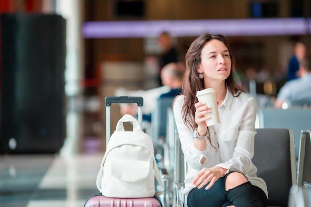 Молодая женщина с кофе в зале ожидания аэропорта ожидания самолета. Premium Фотографии