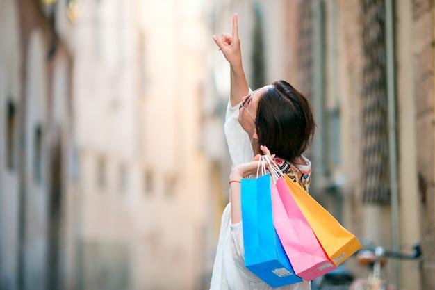 ヨーロッパの狭い通りに買い物袋を持つ少女。笑顔の買い物袋を保持している美しい幸せな女性の肖像画 Premium写真