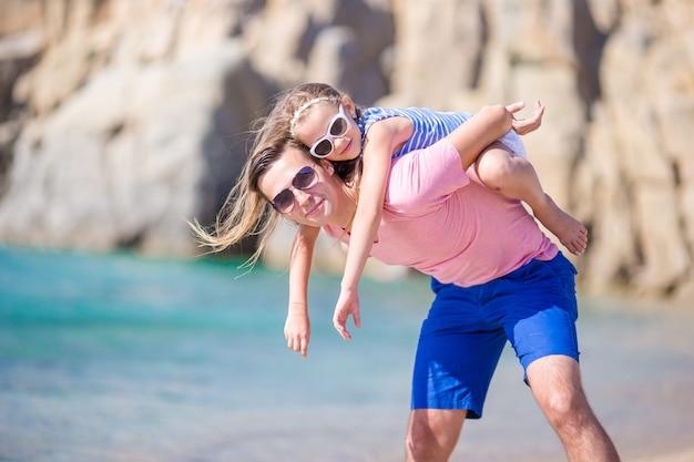 幸せな父と楽しんで熱帯のビーチで彼の愛らしい小さな娘 Premium写真