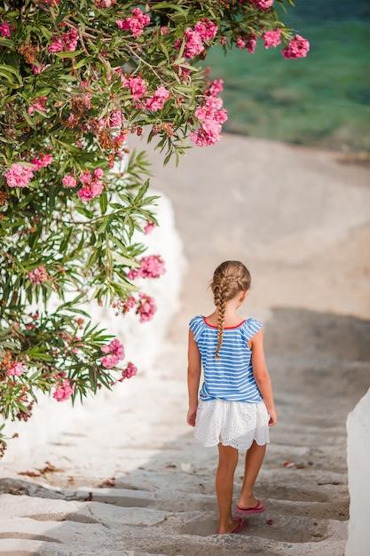 Милая девушка в голубых платьях развлекается на улице на улицах миконоса Premium Фотографии