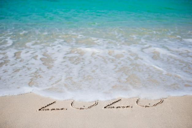 С новым годом написано на белом песке Premium Фотографии