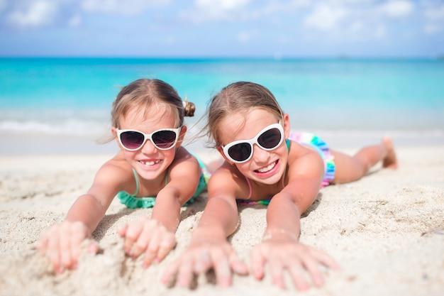 砂浜のビーチで女の子を閉じます。暖かい白い砂浜のビーチで横になっている幸せな子供たち Premium写真