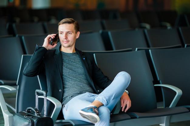 Городской бизнесмен говоря на умном телефоне путешествуя внутрь в авиапорте. молодой человек с мобильным телефоном на посадке авиапорта ждать. Premium Фотографии