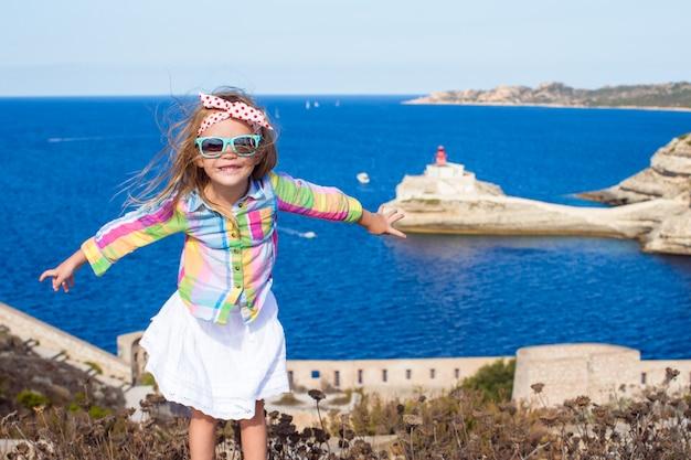 ボニファシオの端の背景の青い海のかわいい女の子 Premium写真