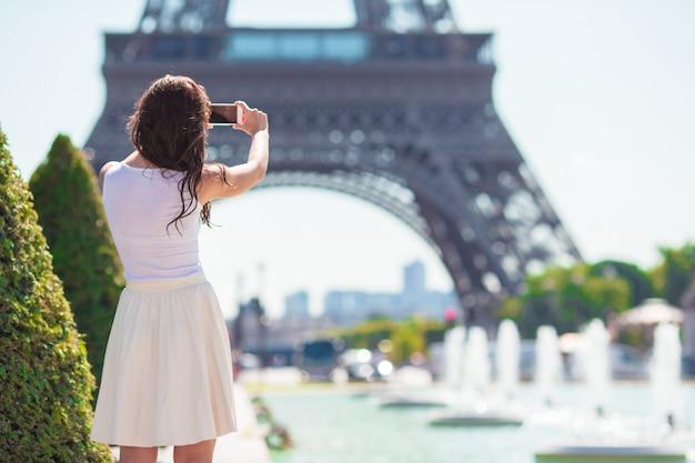 パリの美しい女性が夏休み中にエッフェル塔を背景します。 Premium写真
