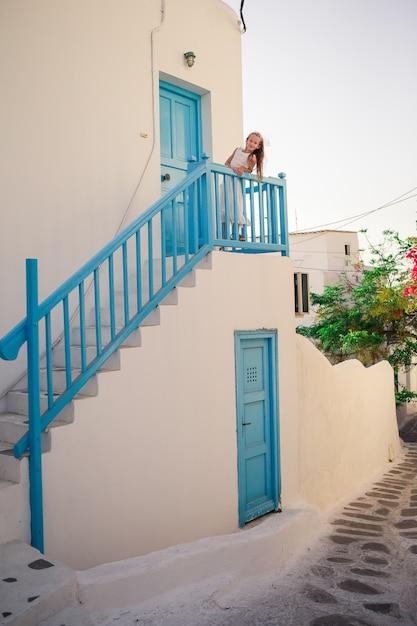 白い壁とカラフルなドアのある典型的なギリシャの伝統的な村の通りで子供します。 Premium写真