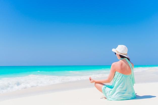 ビーチで瞑想の若い美しい女性 Premium写真