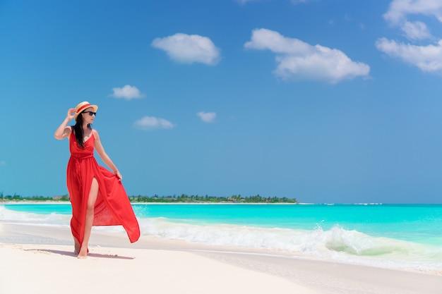 海岸の美しい赤いドレスの少女 Premium写真