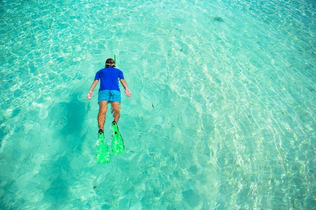 澄んだ熱帯のターコイズブルーの海でシュノーケリングの若い男 Premium写真