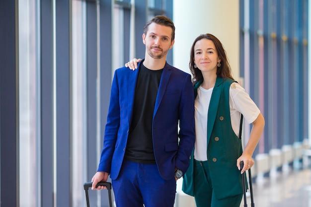 Пара с багажом в международном аэропорту спешит на рейс на посадку. мужчина и женщина смотрят на свои часы в помещении возле большого окна Premium Фотографии