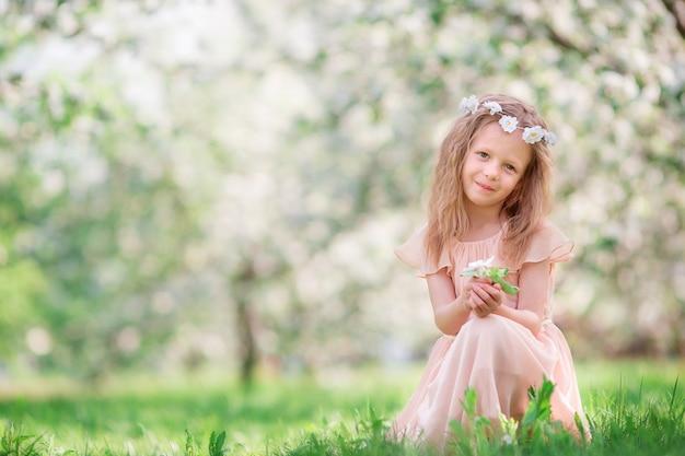 屋外に咲く桜の木の庭の少女 Premium写真