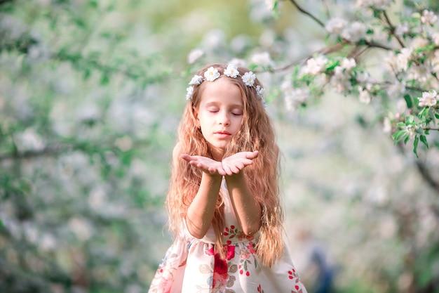 屋外に咲く桜の木の庭で愛らしい少女の肖像画 Premium写真