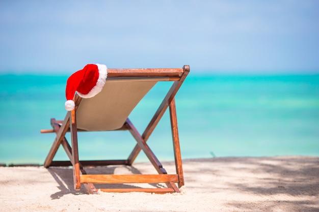 ビーチのクリスマス-海でサンタの帽子が付いている椅子。クリスマス休暇の概念 Premium写真