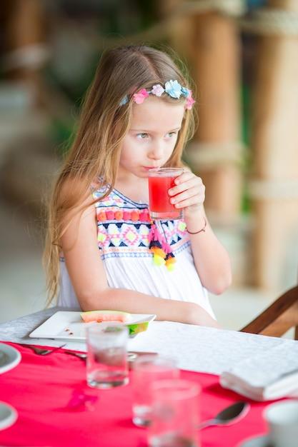 屋外カフェで朝食を持っている小さな子供。朝食を楽しんでいる新鮮なスイカジュースを飲む愛らしい少女。 Premium写真