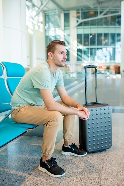 航空機を待っている空港ラウンジで若い男。 Premium写真