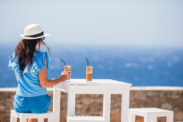 Молодая женщина, пить холодный кофе, наслаждаясь видом на море. красивая женщина расслабиться во время экзотических каникул на пляже, наслаждаясь фраппе Premium Фотографии