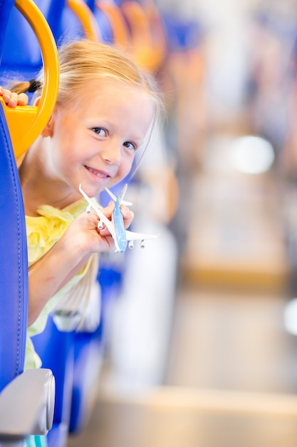 電車の中で旅行や飛行機のモデルを手で楽しんでのかわいい女の子 Premium写真