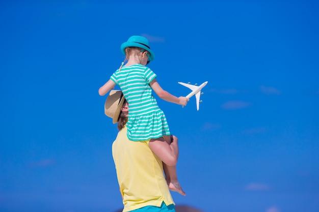 Молодой человек и маленькая девочка с миниатюрой самолета на пляже Premium Фотографии