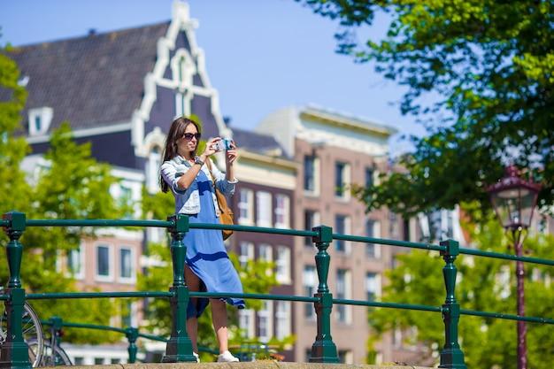 Молодая женщина турист, принимая фото на красивый вид на европейский город с камерой мобильного смартфона Premium Фотографии