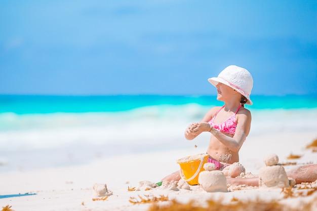 Маленькая прелестная девушка играя на пляже с шариком Premium Фотографии