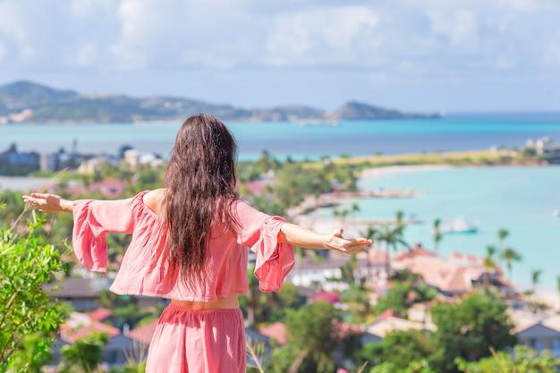 カリブ海の熱帯の島の湾の景色を持つ若い観光客女性 Premium写真
