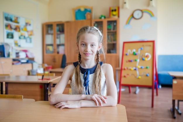Прелестная маленькая школьница с примечаниями и карандашами напольными. Premium Фотографии