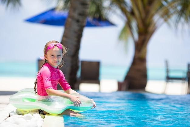 Улыбающаяся очаровательная девушка веселится в открытом бассейне Premium Фотографии