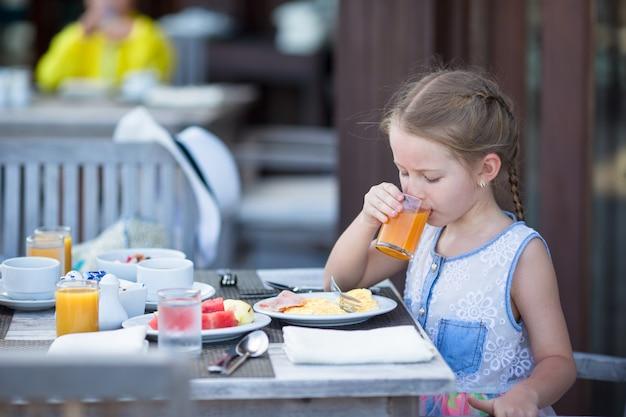 屋外カフェで朝食にリンゴジュースを飲むのかわいい女の子 Premium写真