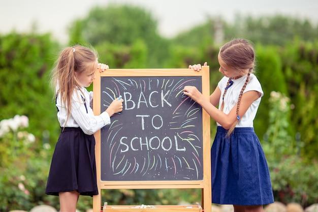Счастливые маленькие школьницы с доске на открытом воздухе Premium Фотографии