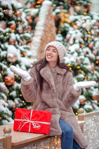 飾られたリビングルームの暖炉でクリスマスジンジャーブレッドの家を作る女の子。 Premium写真