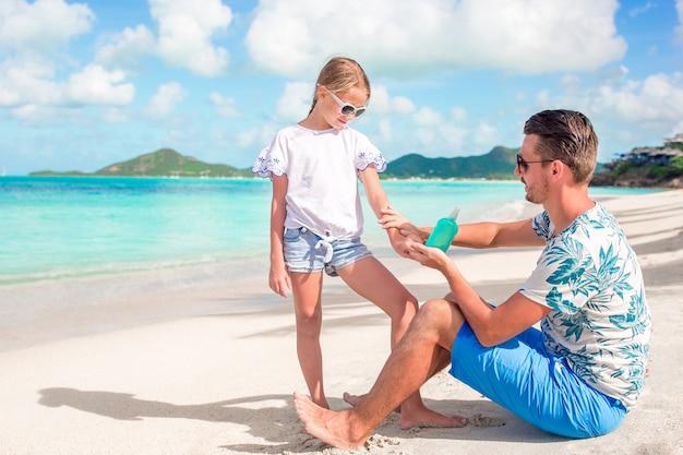 Молодой отец, применяя солнцезащитный крем для дочери нос на пляже. Premium Фотографии