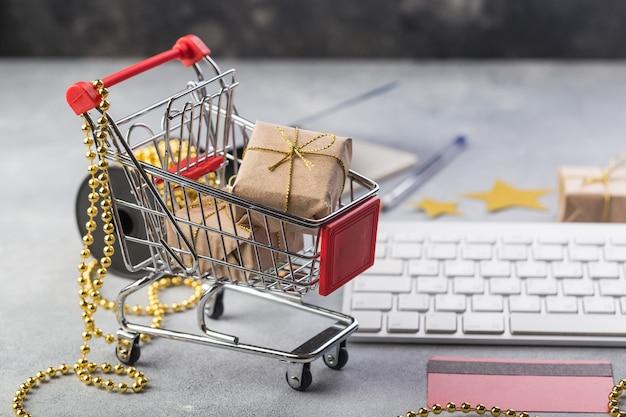 インターネットオンラインショッピングコンセプトクリスマスプレゼント用のキーボードと小さな赤いショッピングカート Premium写真