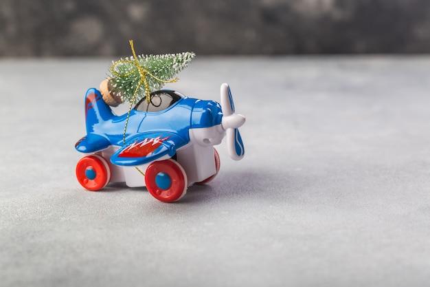 灰色のクリスマスツリーと小さな飛行機 Premium写真