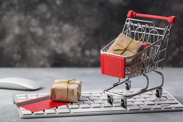 プレゼントとラップトップキーボードの概念上のクレジットカードの小さなショッピングカート Premium写真