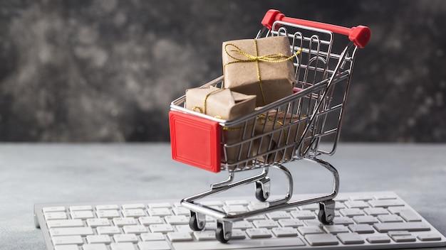 オンラインショッピングに関するラップトップキーボードの概念上のプレゼントとクレジットカードの小さなショッピングカート Premium写真