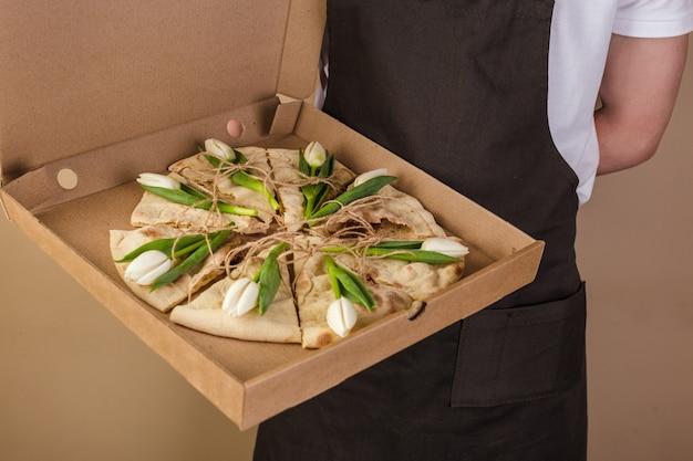 ウェイターによって提供される紙箱の花チューリップと創造的なピザ Premium写真