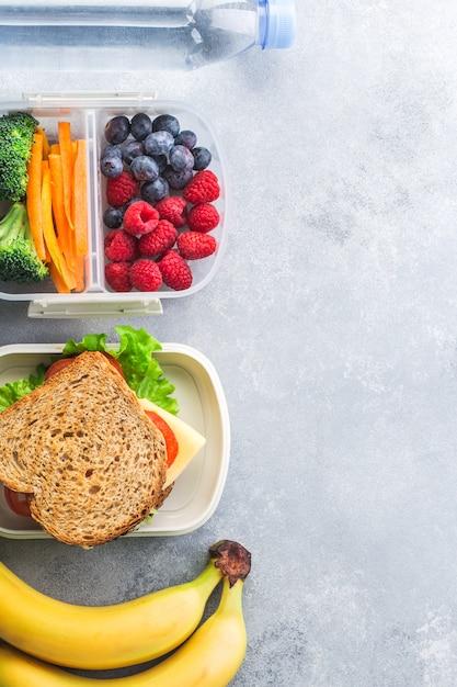 Коробка школьного обеда с бананом ягод сандвича овощей на сером столе здоровой Premium Фотографии