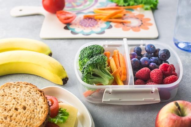健康的なグレーのテーブルに野菜果実バナナと学校のランチボックス Premium写真