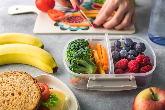 Мать нарезает овощи на ланч-бокс для школы по утрам Premium Фотографии