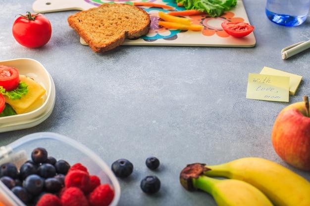 Ланч-бокс с бутербродом, ягодами банана и нарезанной морковью на сером пространстве для текста Premium Фотографии