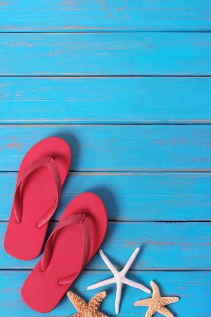 フリップフロップヒトデ夏海岸青い木製の背景の垂直 無料写真