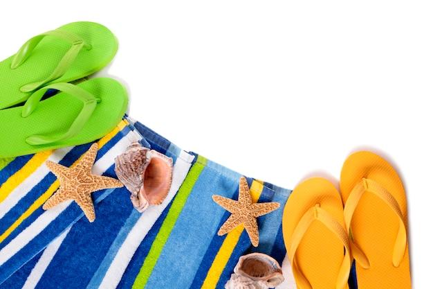 フリップフロップ、ヒトデ、貝殻を白で隔離されるビーチタオル。 無料写真