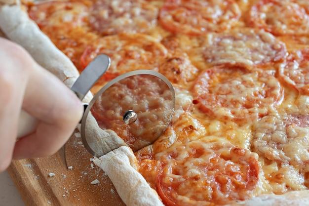 子供はローラーカッターでピザを切るクローズアップ Premium写真