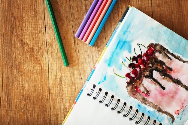 テーブルの上に色鉛筆とチェリーとケーキの水彩画が描かれています。側面図 Premium写真