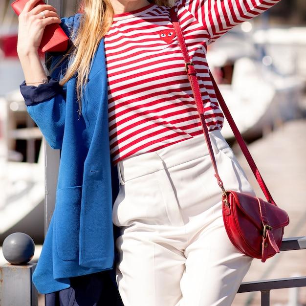 白いズボン、青いジャケットとストライプのセーター、ポーズをとる女性 Premium写真