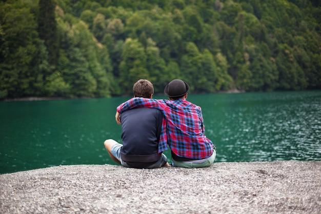 Молодая пара путешественников любуется горным озером, вид сзади Premium Фотографии